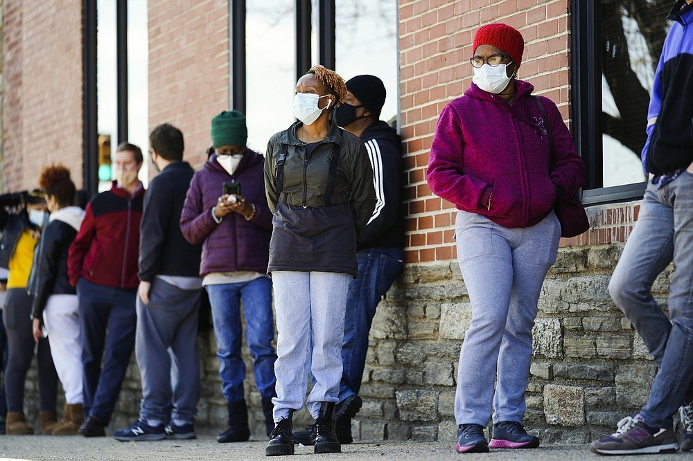 FILE - In this March 29, 2021, file photo, people wearing face masks as a precaution against the coronavirus wait in line to receive COVID-19 vaccines at a site in Philadelphia. Nearly half of new coronavirus infections nationwide are in just five states, including Pennsylvania — a situation that puts pressure on the federal government to consider changing how it distributes vaccines by sending more doses to hot spots. (AP Photo/Matt Rourke, File)