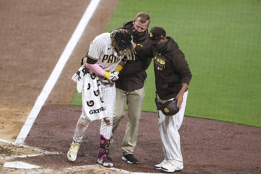 San Diego Padres manger Jayce Tingler, right, and a trainer, center, help Fernando Tatis Jr., left, off the field after Tatis hurt his shoulder while swinging at a pitch in the third inning of a baseball game against the San Francisco Giants, Monday, April 5, 2021, in San Diego. (AP Photo/Derrick Tuskan)