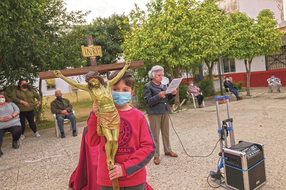 Catholic worshipers attend a religious event outside Nuestra Senora de la Candelaria church in Seville, southern Spain, Friday, Feb. 26, 2021. Few Catholics in devout southern Spain would have imagined an April without the pomp and ceremony of Holy Week processions. With the coronavirus pandemic unremitting, they will miss them for a second year. (AP Photo/Laura Leon)