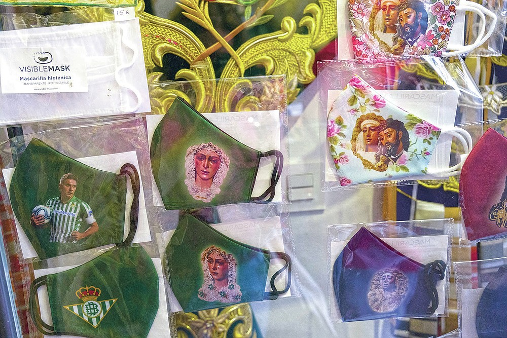 Face masks with images of Jesus, Virgin Mary and soccer players are displayed in a shop during the Holy Week in Seville, southern Spain, Tuesday, March 30, 2021. Few Catholics in devout southern Spain would have imagined an April without the pomp and ceremony of Holy Week processions. With the coronavirus pandemic unremitting, they will miss them for a second year. (AP Photo/Laura Leon)