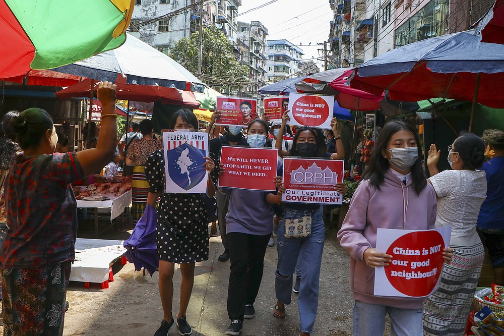 Anti-coup protesters hold slogans as they are greeted while marching along a market street in Yangon, Myanmar, Wednesday April 7, 2021. Threats of lethal violence and arrests of protesters have failed to suppress daily demonstrations across Myanmar demanding the military step down and reinstate the democratically elected government. (AP Photo)