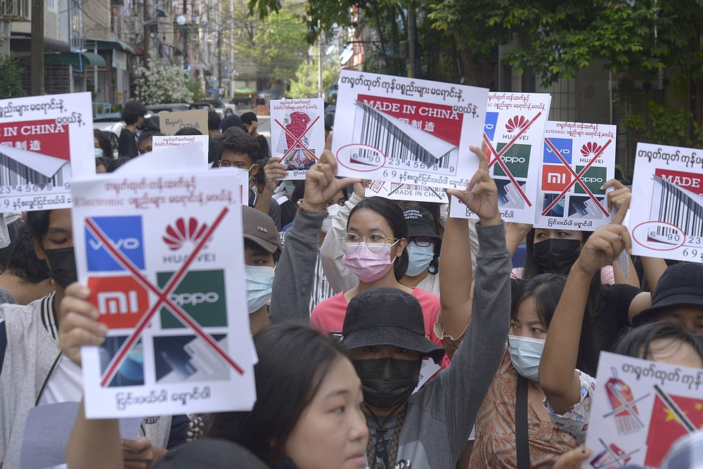 Anti-coup protesters hold slogans calling for a boycott of Chinese products during a demonstration in Yangon, Myanmar on Wednesday, April 7, 2021. Protesters continue to hold daily demonstrations in some parts of Myanmar despite threats from government forces of arrest and dispersal as they rally against the Feb. 1 military coup that ousted the civilian government of Aung San Suu Kyi. (AP Photo)