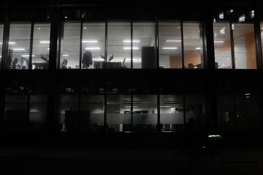 "Lights shine from empty offices in the Barbican area of the City of London, Saturday, March 6, 2021. When the pandemic struck, about 540,000 workers vanished from London's financial hub almost overnight. The area known as ""the City"" became a ghost town as many people began working from home. A year on, most haven't returned to the business hub. (AP Photo/Alastair Grant)"