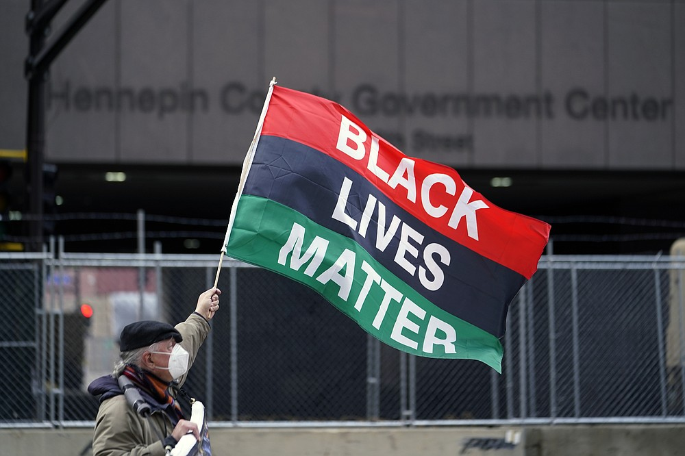 A protesters waves a Black Lives Matter flag across the street from the Hennepin County Government Center, Wednesday, April 7, 2021, in Minneapolis where testimony continues in the trial of former Minneapolis police officer Derek Chauvin continues. Chauvin is charged with murder in the death of George Floyd during an arrest last May in Minneapolis. (AP Photo/Jim Mone)