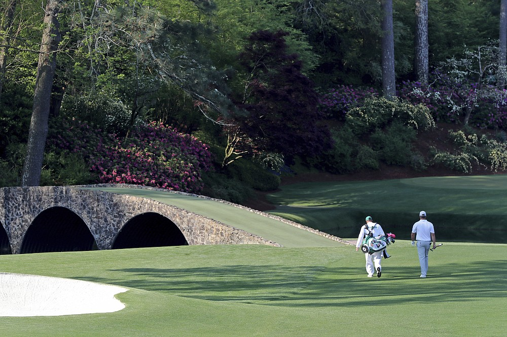 Bryson DeChambeau and his caddy Tim Tucker walks toward the Ben Hogan bridge and the 12th hole during a practice round for the Masters golf tournament in Augusta, Ga., Wednesday, April 7, 2021. (Curtis Compton/Atlanta Journal-Constitution via AP)