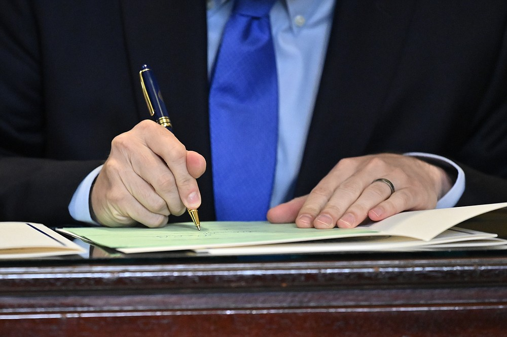 Kentucky Governor Andy Beshear signs a bill related to the American Rescue Plan Act in the Rotunda of the Kentucky State Capitol in Frankfort, Ky., Wednesday, April 7, 2021. (AP Photo/Timothy D. Easley)