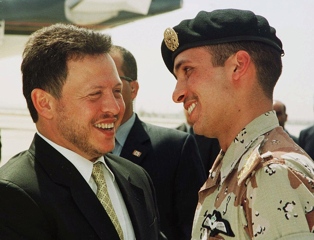 FILE - In this April 2, 2001, file photo, Jordan's King Abdullah II laughs with his half brother Prince Hamzah, right, shortly before the monarch embarked on a tour of the United States. Abdullah and Hamzah are both sons of the beloved King Hussein, who ruled Jordan for nearly a half-century before his death in 1999. Abdullah had appointed Hamzah as crown prince upon his succession but stripped him of the title in 2004. (AP Photo/Yousef Allan, File)