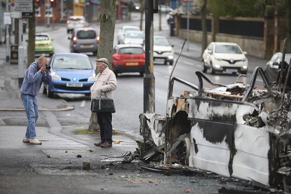 A man poses to get his picture taken next to a burnt out bus on the Shankill road in West Belfast, Northern Ireland, Thursday, April 8, 2021. It follows another night of violence in Loyalist areas that has now spread to interface areas of the peace divide. (AP Photo/Peter Morrison)