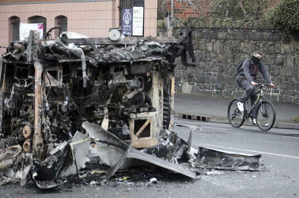 A cyclist passes the remains of a burnt out bus on the Shankill road in West Belfast, Northern Ireland, Thursday, April 8, 2021. It follows another night of violence in Loyalist areas that has now spread to interface areas of the peace divide. (AP Photo/Peter Morrison)
