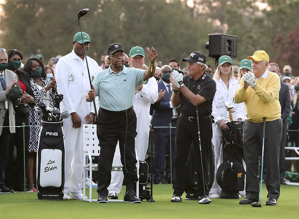 Honorary starter Lee Elder, left, gestures as he is introduced and applauded by honorary starters Gary Player and Jack Nicklaus, right, before the ceremonial tee shots to begin the Masters golf tournament at Augusta National Golf Club in Augusta, Ga., Thursday, April 8, 2021. (Curtis Compton/Atlanta Journal-Constitution via AP)
