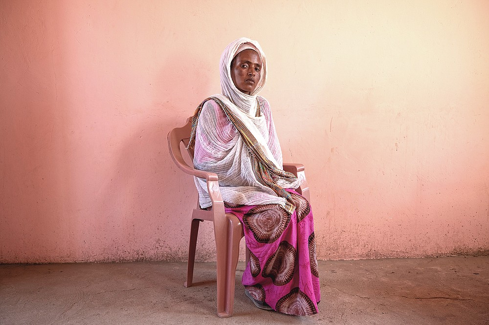 """Tigrayan refugee Alem Mebrahtu, 30, who fled the conflict in Ethiopia's Tigray, sits for a portrait in eastern Sudan, near the border with Ethiopia, on March 15, 2021. Bodies were strewn near the riverbank, she said. """"Some were face-down. Some were looking up at the sky."""" She estimated some 50 corpses. (AP Photo/Nariman El-Mofty)"""