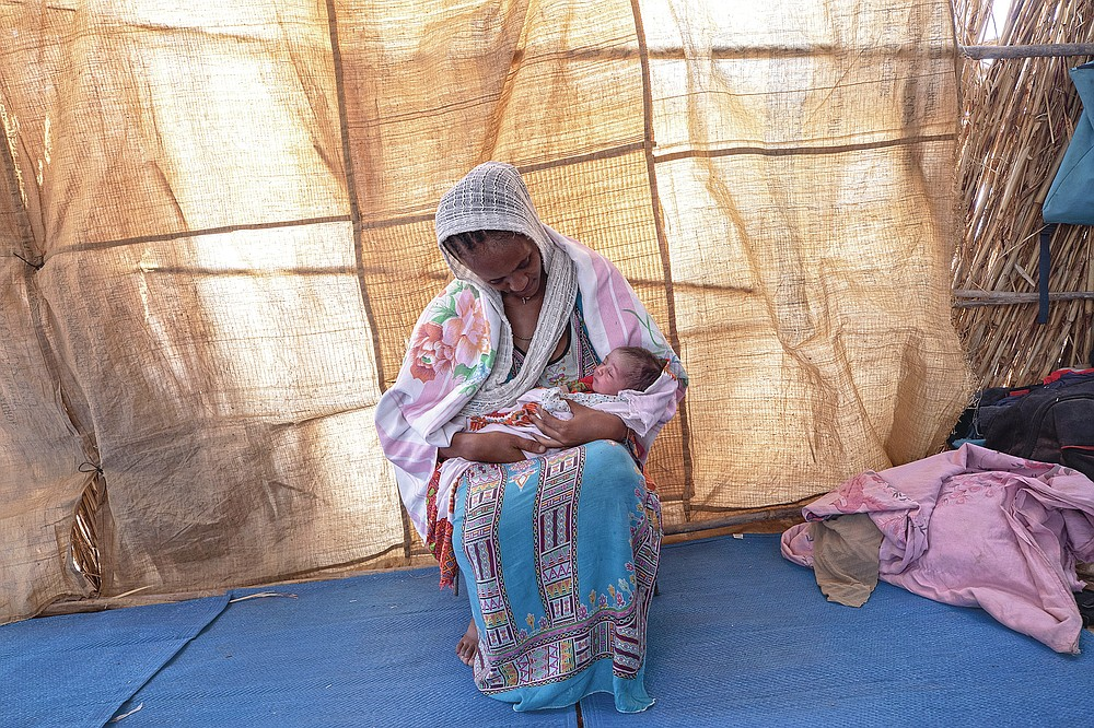 """Lemlem Gebrehiwet, a 20-year-old Tigrayan refugee, holds her 3-day-old daughter, Semhal, in their shelter in Hamdayet, eastern Sudan, near the border with Ethiopia, on March 16, 2021. Other Tigrayans were turned away because of who they were. """"They started distributing new ID cards in Bahkar but only for Amhara and Wolkait,"""" said Gebrehiwet, who fled while heavily pregnant and gave birth three days after reaching Sudan. (AP Photo/Nariman El-Mofty)"""