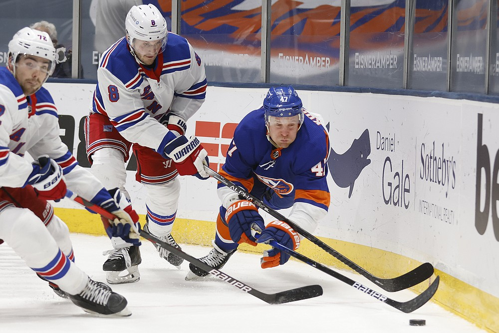 New York Islanders' Noah Dobson (8) lunges for the puck against New York Rangers' Jacob Trouba (8) and Filip Chytil (72), of the Czech Republic, during the second period of an NHL hockey game Friday, April 9, 2021, in Uniondale, N.Y. (AP Photo/Jason DeCrow)