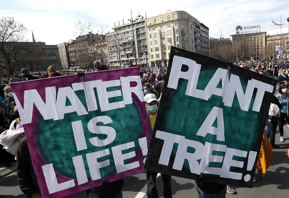 People hold banners during a protest in front of the Serbian Parliament building in Belgrade, Serbia, Saturday, April 10, 2021. Environmental activists are protesting against worsening environmental situation in Serbia. (AP Photo/Darko Vojinovic)