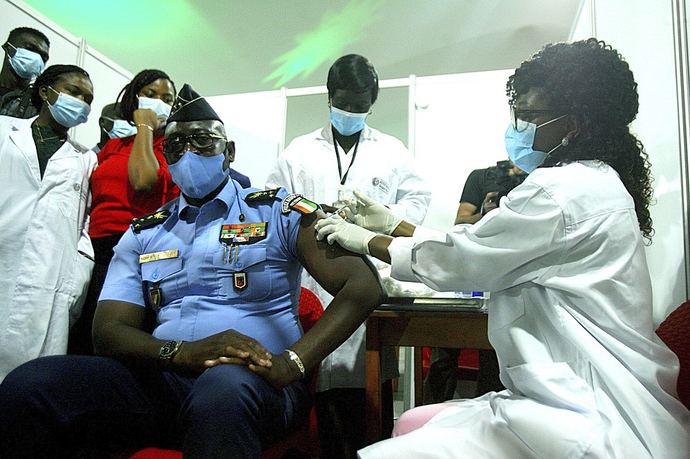FILE - In this March 1, 2021, file photo, Youssouf Kouyate, National Police General Director, receives a shot of the AstraZeneca vaccine in Abidjan, Ivory Coast. The COVAX global initiative is providing vaccines to poorer countries lacking the clout to negotiate for them on their own, but on March 25, COVAX announced a major setback in its vaccine rollout because a surge in infections in India had caused the Serum Institute of India to cater to domestic demand, resulting in a delay in global shipments of up to 90 million doses. (AP Photo/Diomande Ble Blonde, File)