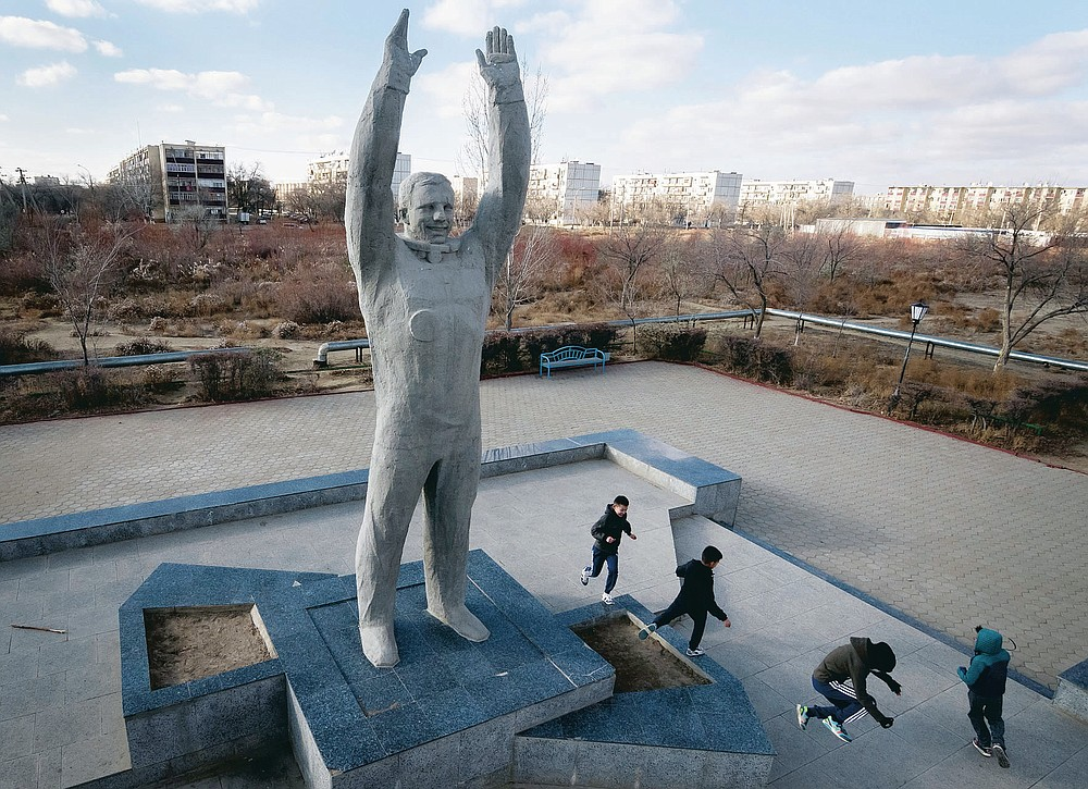 FILE - In this Sunday, Nov. 13, 2016 file photo, children play near a sculpture of the first cosmonaut Yuri Gagarin at the Russian leased Baikonur cosmodrome, the world's first and largest operational space launch facility, in Baikonur, Kazakhstan. From a giant statue towering over Moscow to a more modest monument on the Sakhalin Island in the Pacific Ocean, dozens of memorials across Russia commemorate Yuri Gagarin, the cosmonaut who became the first person in space on April 12, 1961, 60 years ago. (AP Photo/Dmitri Lovetsky, File)