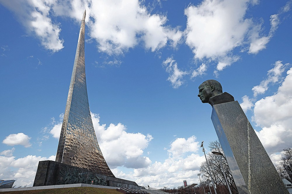 The bust of Yuri Gagarin, right, and the 107-meter (351-feet) high titanium obelisk depicting a starting rocket dedicated to the first cosmonauts, in Moscow, Russia, Friday, April 9, 2021. From a giant statue towering over Moscow to a more modest monument on the Sakhalin Island in the Pacific Ocean, dozens of memorials across Russia commemorate Yuri Gagarin, the cosmonaut who became the first person in space on April 12, 1961, 60 years ago. (AP Photo/Alexander Zemlianichenko)