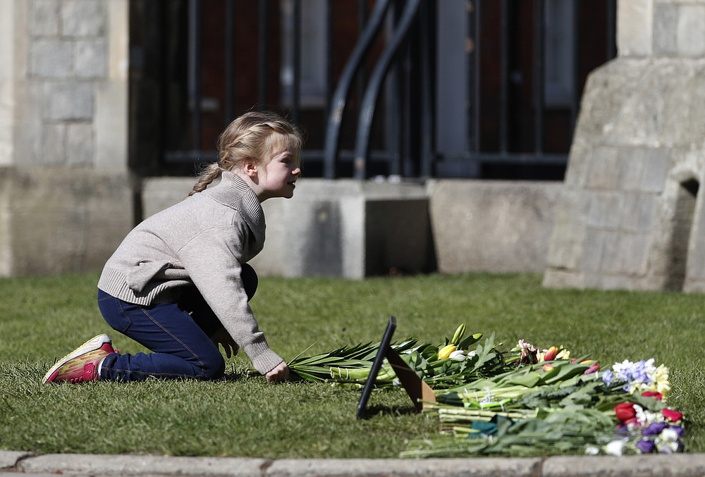 A young girl lays flowers as a tribute to Britain's Prince Philip outside Windsor Castle, Windsor, England, Tuesday, April 13, 2021. Britain's Prince Philip, husband of Queen Elizabeth II, died Friday April 9 aged 99. His funeral service will take place on Saturday at Windsor Castle. (AP Photo/Alastair Grant)