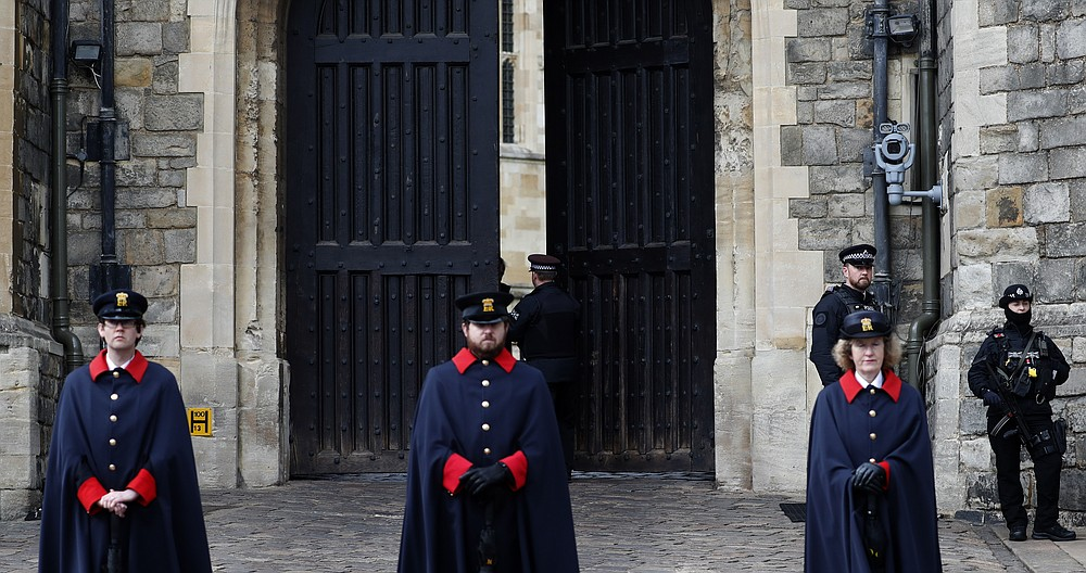 The King Henry VIII gates are tested to open and close at Windsor Castle guarded by armed police and casket wardens in Windsor, England, Tuesday, April 13, 2021. Prince Philip, husband of Britain's Queen Elizabeth II died Saturday April 10, aged 99, and his funeral will take place in Windsor upcoming Saturday. (AP Photo/Alastair Grant)