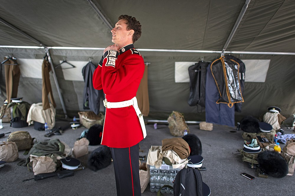 A member of the Coldstream Guards prepares his uniform before rehearsing for Britain's Prince Philip's funeral on the Drill Square at the Army Training Centre Pirbright in Woking, Surrey, England Wednesday April 14, 2021. Prince Philip's funeral will be held at Windsor Castle on Saturday following his death at the age of 99 on April 10. (Victoria Jones/PA via AP)