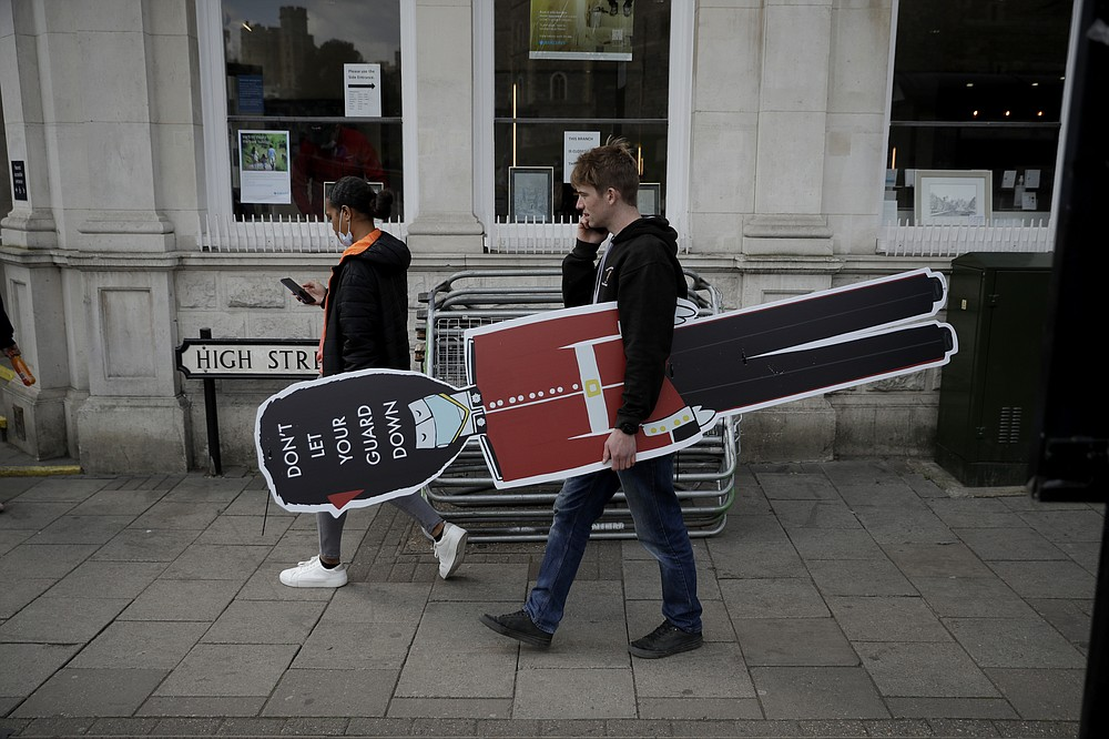 A worker carries a cutout of a guardsman, with a warning to remind people not to let their guard down with regards to coronavirus, as he looks for a suitable place to put it up, to coincide with non-essential shops being reopened this week, opposite Windsor Castle, in Windsor, England, Wednesday, April 14, 2021. Britain's Prince Philip, husband of Queen Elizabeth II, died Friday April 9 aged 99. His funeral service will take place on Saturday at Windsor Castle. (AP Photo/Matt Dunham)