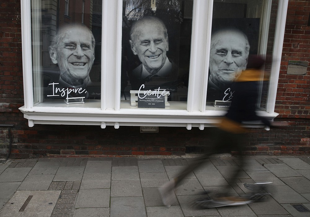 Portraits of the Prince Philip Duke of Edinburgh are displayed in the window of an art gallery following the death of the Duke of Edinburgh at the age of 99, in Windsor, England, Tuesday April 13, 2021.  The funeral for Prince Philip is scheduled for upcoming Saturday. (Steve Parsons/PA via AP)