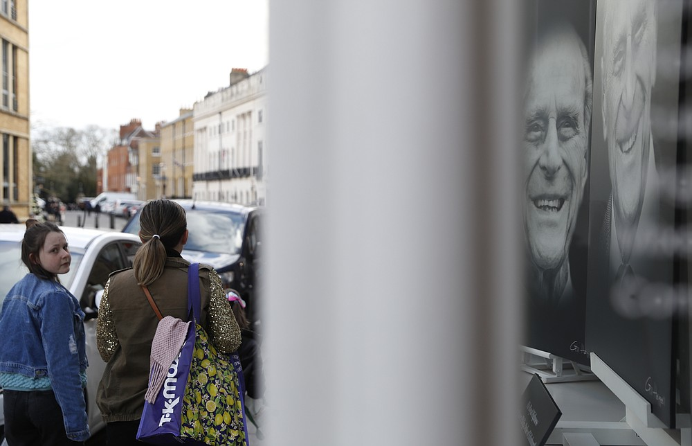 A shop displays a triptych of photos of Prince Philip in Windsor, England, Tuesday, April 13, 2021. Britain's Prince Philip, husband of Queen Elizabeth II, died Friday April 9 aged 99. His funeral service will take place on Saturday at Windsor Castle. (AP Photo/Alastair Grant)