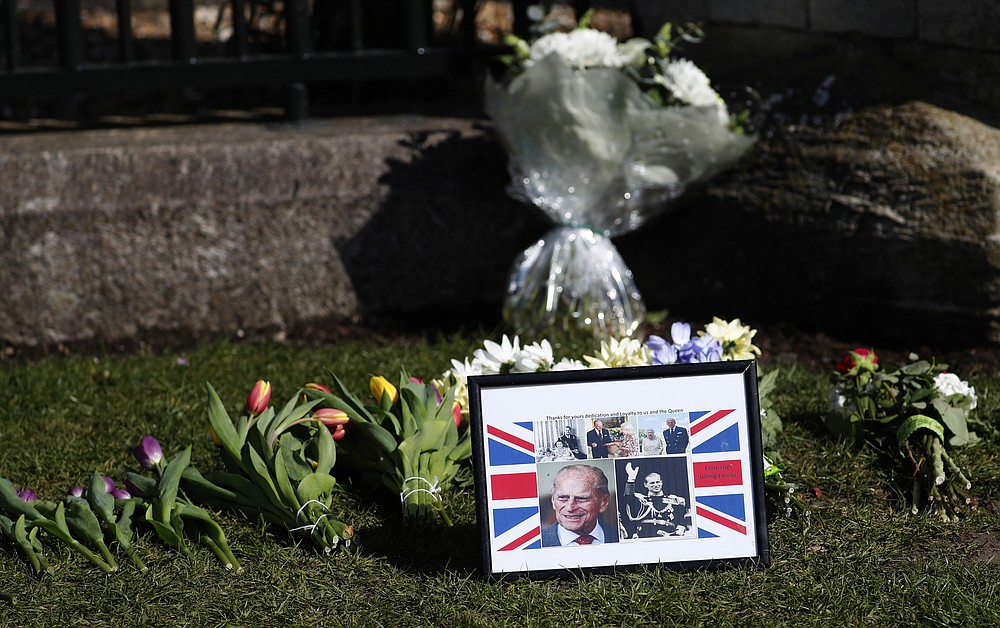 Tributes are laid outside Windsor Castle Windsor, England, Tuesday, April 13, 2021. Britain's Prince Philip, husband of Queen Elizabeth II, died Friday April 9 aged 99. His funeral service will take place on Saturday at Windsor Castle. (AP Photo/Alastair Grant)