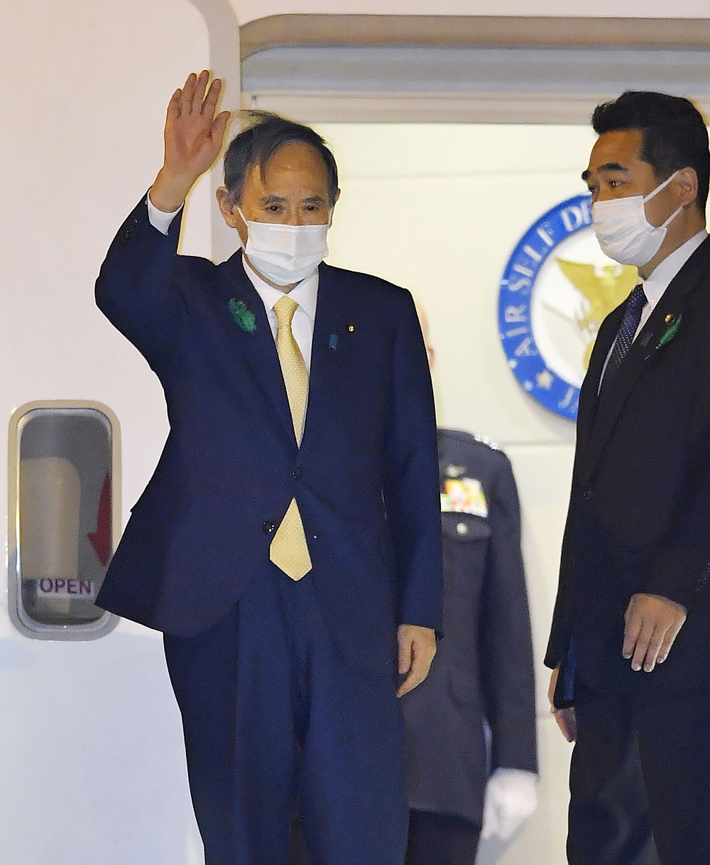 Japanese Prime Minister Yoshihide Suga waves on his departure for the U.S., at Haneda airport, in Tokyo Thursday, April 15, 2021.  Suga headed to Washington on Thursday to become a first foreign leader to have a face-to-face meeting with President Joe Biden for talks that would reaffirm the strength of their alliance and how to deal with China's growing assertiveness and challenge to democratic values. (Kyodo News via AP)