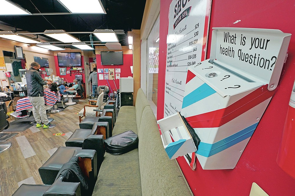 A box encouraging barber shop patrons to submit health questions is displayed at The Shop, Friday, April 9, 2021, in Hyattsville, Md. Barbers are member of the Health Advocates In Reach & Research (HAIR) program, which helps barbers and hair stylists to get certified to talk to community members about health. During the COVID-19 pandemic, a team of certified barbers have been providing factual information to customers about vaccines, a topic that historically has not been trusted by members of black communities because of the health abuse the race has endured over the years. (AP Photo/Julio Cortez)