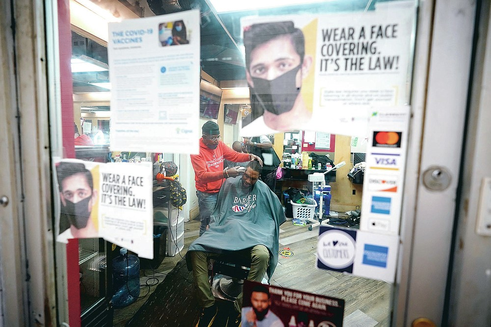 Health literature is posted on a door as Kevin Fitzhugh, center left, cuts the hair of Ikemba Orusakwe, Friday, April 9, 2021, in Hyattsville, Md. Barbers such as Fitzhugh are members of the Health Advocates In Reach & Research (HAIR) program, which helps barbers and hair stylists to get certified to talk to community members about health. During the COVID-19 pandemic, a team of certified barbers have been providing factual information to customers about vaccines, a topic that historically has not been trusted by members of black communities because of the health abuse the race has endured over the years. (AP Photo/Julio Cortez)