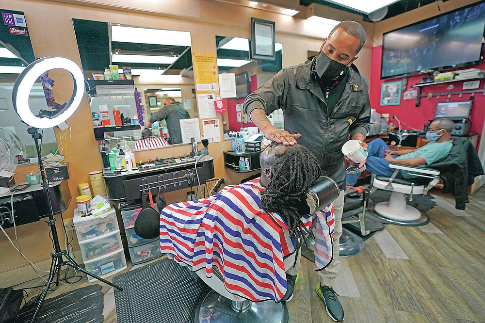 Mike Brown, right, a barber and health advocate, lines up the facial hair of Vyron Cox Jr., Friday, April 9, 2021, in Hyattsville, Md. Brown is a member of the Health Advocates In Reach & Research (HAIR) program, which helps barbers and hair stylists to get certified to talk to community members about health. During the COVID-19 pandemic, Brown and a team of certified barbers have been providing factual information to customers about vaccines, a topic that historically has not been trusted by members of black communities because of the health abuse the race has endured over the years. (AP Photo/Julio Cortez)