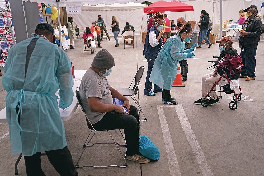 FILE - In this Feb. 10, 2021, file photo, Viola Roberson, 75, far right, and 61-year-old Mark McNamee, foreground, wait for their COVID-19 vaccine at a vaccination site set up in the parking lot of the Los Angeles Mission in the Skid Row area of Los Angeles. While older homeless adults were eligible for vaccination in many states earlier this year, the shots now are finally reaching thousands of younger adults who are homeless.  (AP Photo/Jae C. Hong, File)