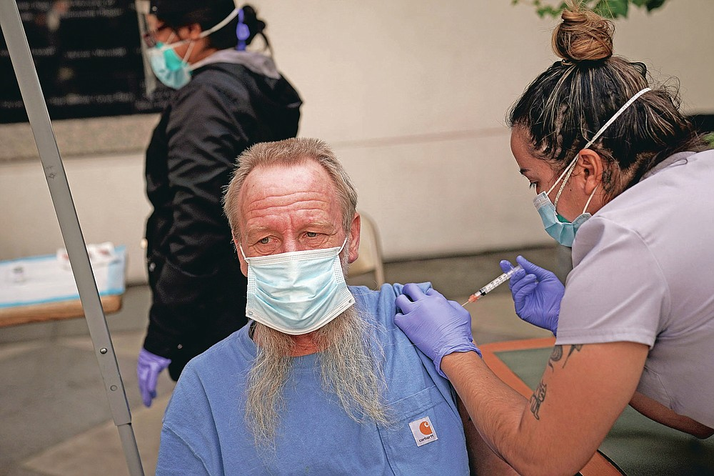FILE - In this Feb. 3, 2021, file photo, EMT Rachel Bryant, right, administers a COVID-19 vaccine to a homeless man in the courtyard of the Midnight Mission in Los Angeles. Homeless Americans who have been left off priority lists for coronavirus vaccinations — or even bumped aside as states shifted eligibility to older age groups — are finally getting their shots as vaccine supplies increase.  (AP Photo/Jae C. Hong)