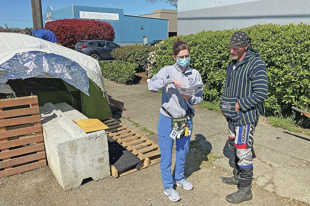 Moira Andrews, a street outreach nurse for Neighborcare Health, speaks with Charles Ussery, 52, who lives in an encampment in the Georgetown neighborhood of Seattle on Monday, April 12, 2021. Andrews spoke with Ussery about the COVID-19 vaccines and answered questions in an effort to vaccinate people experiencing homelessness. Advocates say homeless people are at greater risk of being infected and greater risk of hospitalization and death than the average person, and they should have been prioritized earlier. (AP Photo/Manuel Valdes)