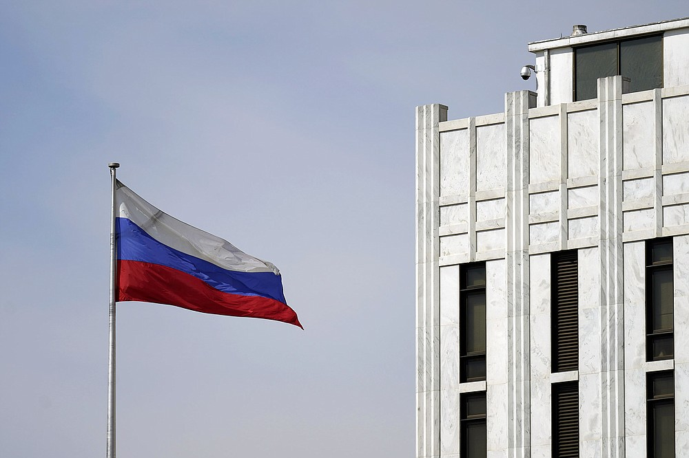 The Russian flag flies Thursday on the grounds of the Russian Embassy in Washington. After the U.S. imposed sanctions Thursday, Russian officials vowed a swift series of retaliatory measures. (AP/Carolyn Kaster)