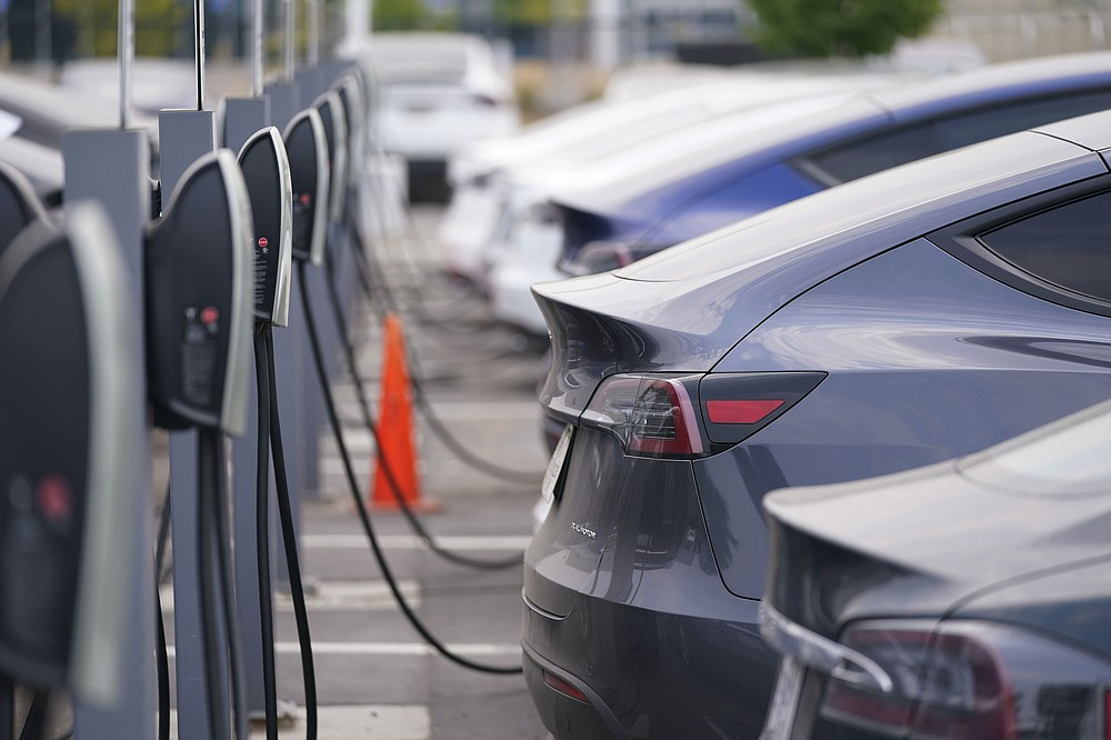 "This Aug. 23, 2020 photo shows a long line of unsold 2020 models charge outside a Tesla dealership in Littleton, Colo.  The European Union is lacking sufficient charging infrastructure for electric vehicles, according to the bloc's external auditor. In a report published Tuesday, April 13, 2021, the European Court of Auditors said users are gaining more harmonized access to charging networks but the EU is still ""a long way from reaching its Green Deal target of 1 million charging points by 2025."" (AP Photo/David Zalubowski)"