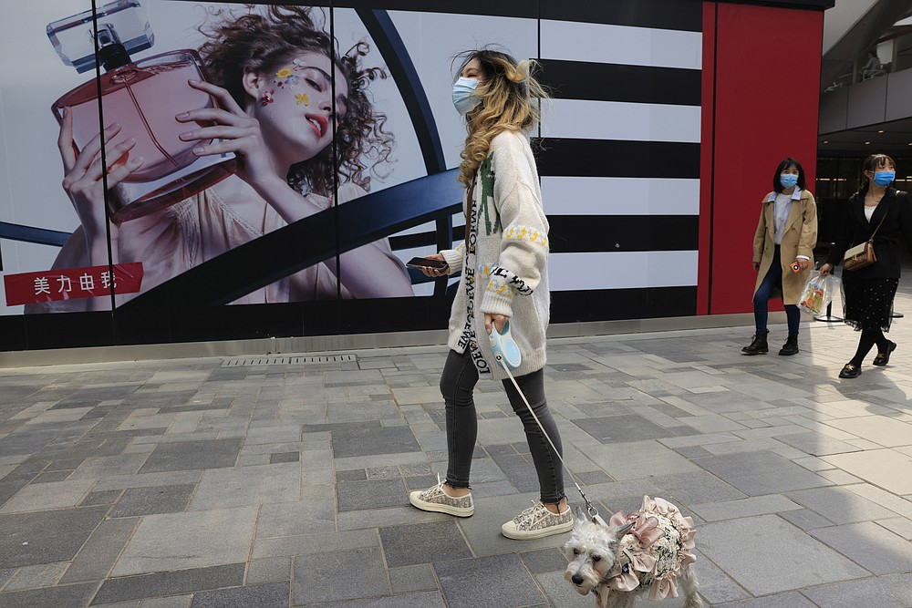 A woman walks her dog in a retail district in Beijing on Thursday, April 15, 2021. China's economic growth surged to 18.3% over a year earlier in the first quarter of this year as factory and consumer activity recovered from the coronavirus pandemic. (AP Photo/Ng Han Guan)