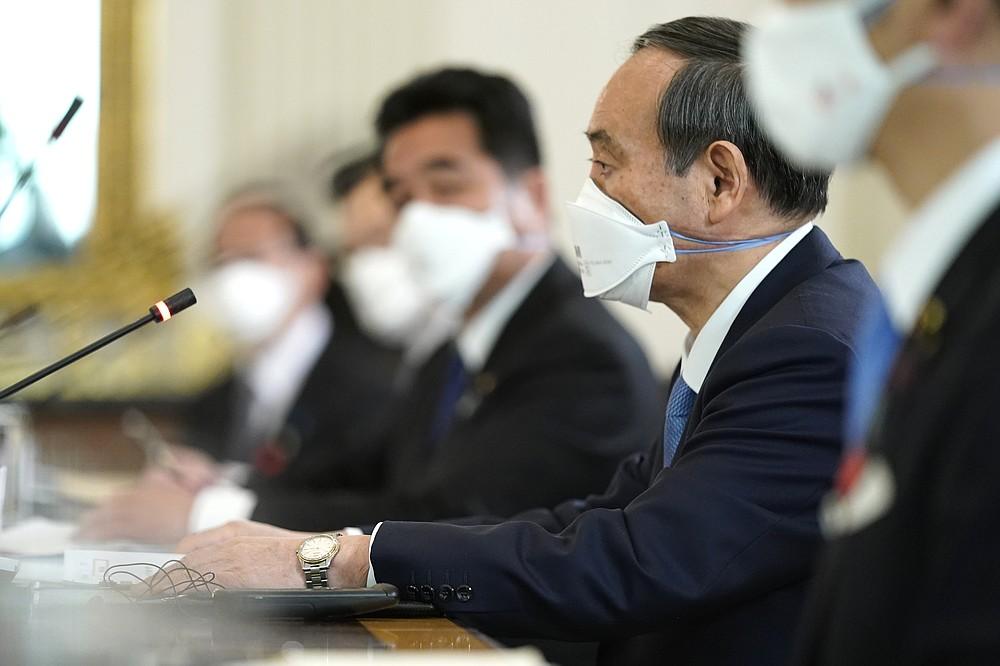 Japanese Prime Minister Yoshihide Suga listens as President Joe Biden speaks in the State Dining Room of the White House, Friday, April 16, 2021, in Washington. (AP Photo/Andrew Harnik)
