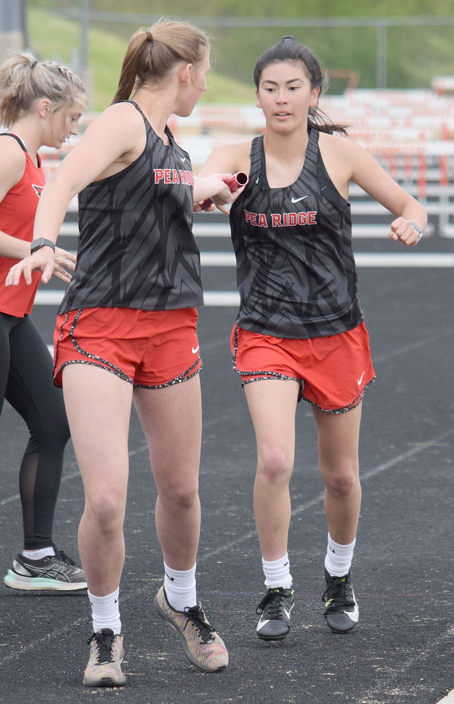 Dallice White receives the baton from Allie King during a relay race in Gravette last week.
