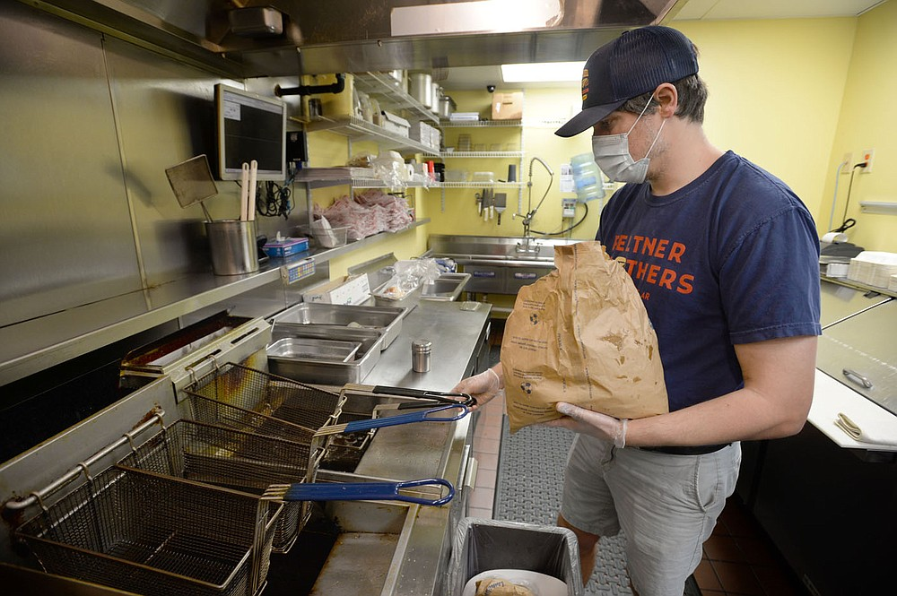 Grant Feltner, co-owner of Feltner Brothers, prepares food Friday, April 23, 2021, at the restaurant in Fayetteville. Hospitality and leisure workers were hit very hard during the pandemic. Visit nwaonline.com/210425Daily/ for today's photo gallery.  (NWA Democrat-Gazette/Andy Shupe)
