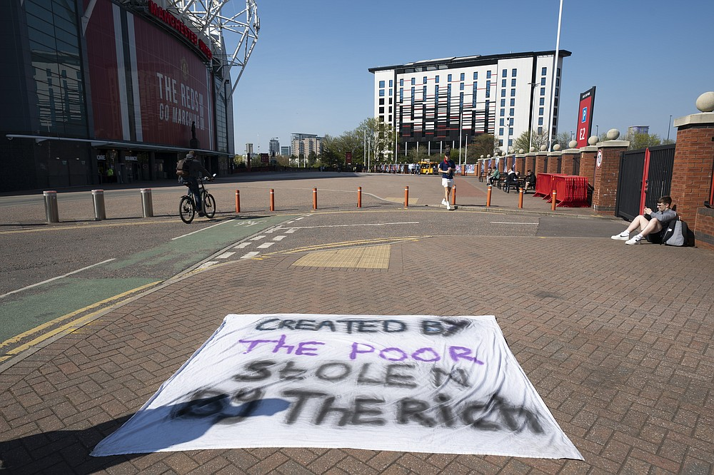 Football supporters place a protest banner outside Manchester United's Old Trafford Stadium, Manchester, England, Monday, April 19, 2021, opposing the formation of the European Super League. Players at the 12 clubs setting up their own Super League could be banned from this year's European Championship and next year's World Cup, UEFA President Aleksander Ceferin said Monday. (AP Photo/Jon Super)