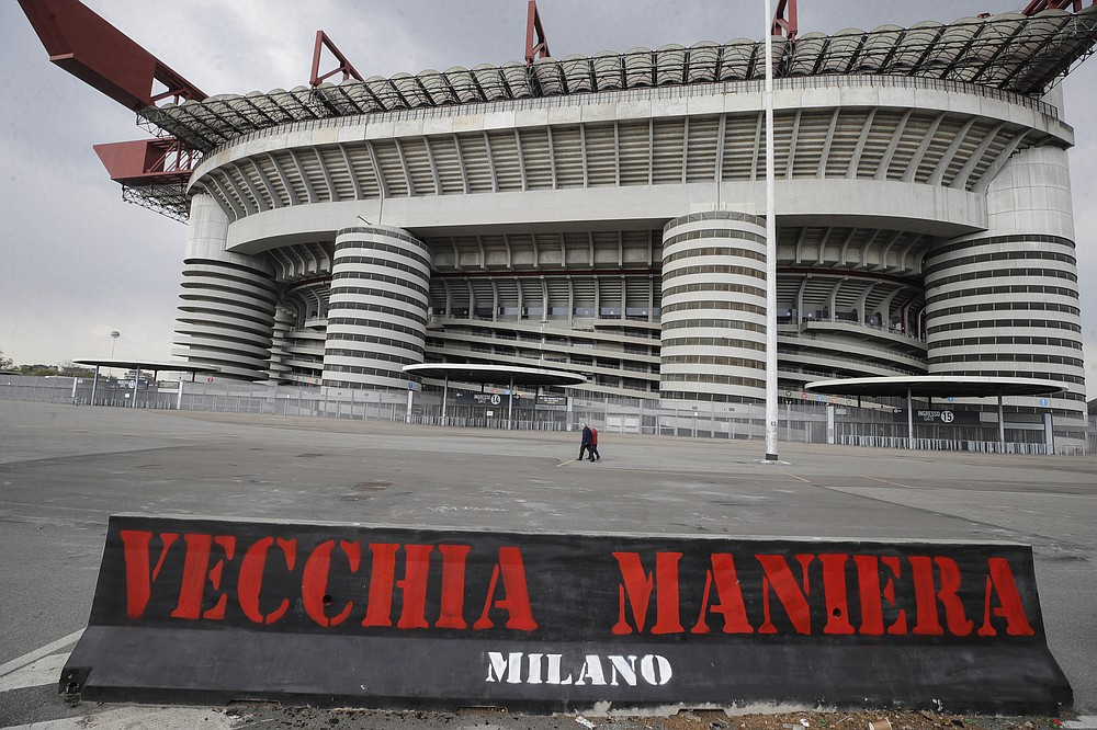 """A banner in the colours of AC Milan and reading in Italian """"Old style"""" is displayed outside the San Siro stadium in Milan, Italy, Monday, April 19, 2021. AC Milan, along with Juventus and Inter Milan, are the three Italian clubs that entered as founding members in the European Super League. The Super League intends to launch a 20-team competition with 15 founding members but only 12 have currently signed up. (AP Photo/Luca Bruno)"""