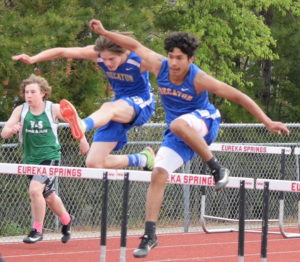 Westside Eagle Observer/MIKE ECKELS Decatur's Brian Ruiz (right) and teammate Dayton McGarrah leap over the bars at nearly the same time during the 300 meter hurdles which were part of the 2A-1 Junior High District Track Meet in Eureka Springs Friday. Ruiz took first place and McGarrah took second in both the 110 and 300 meter hurdles, leading the Decatur boys to a second place finish in the meet.