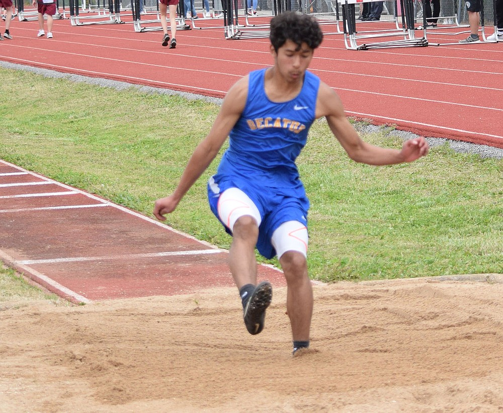Westside Eagle Observer/MIKE ECKELS Brian Ruiz sticks his landing as he leaps to a first place finish in the long jump event which was part of the 2A-1 Junior High District Track Meet in Eureka Springs Friday afternoon.