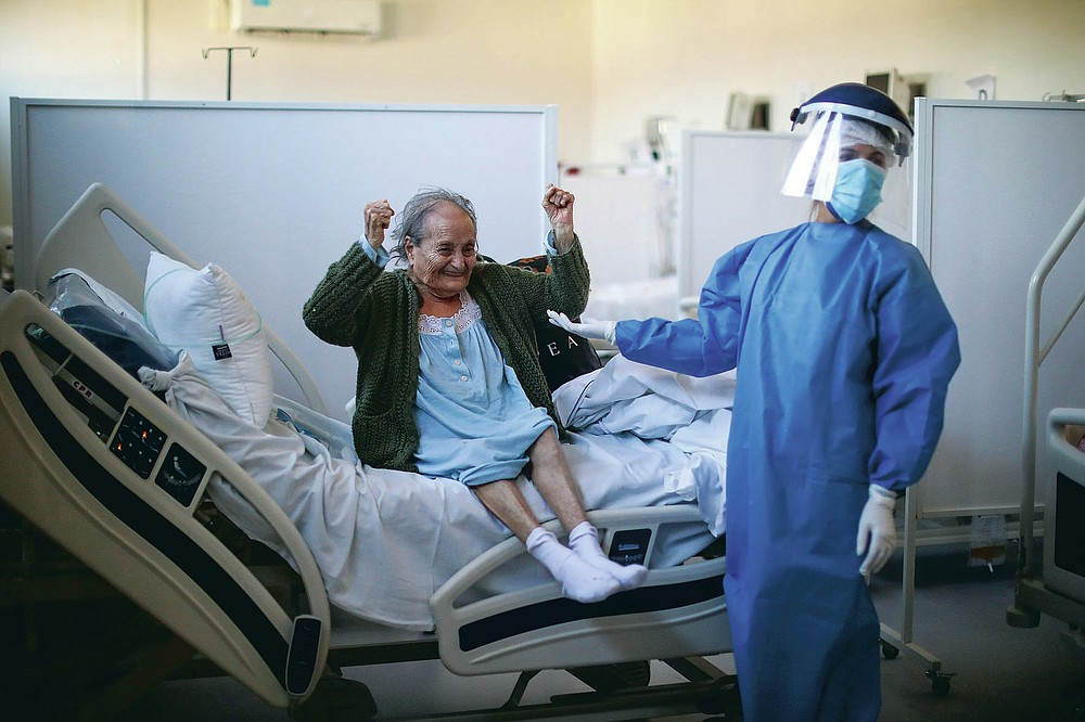 """Blanca Ortiz, 84, celebrates after learning that she will be dismissed from the Eurnekian Ezeiza Hospital, on the outskirts of Buenos Aires, Argentina, Thursday, Aug. 13, 2020, several weeks after being admitted with COVID-19. Photographer Natacha Pisarenko said the moment was one of the few she witnessed in months of covering COVID-19 in which doctors and nurses allowed themselves to feel joy. """"The moment made all of us in the room with her laugh and feel hopeful again,"""" Pisarenko said. """"It was the brightest moment for me while covering such a heavy story."""" (AP Photo/Natacha Pisarenko)"""