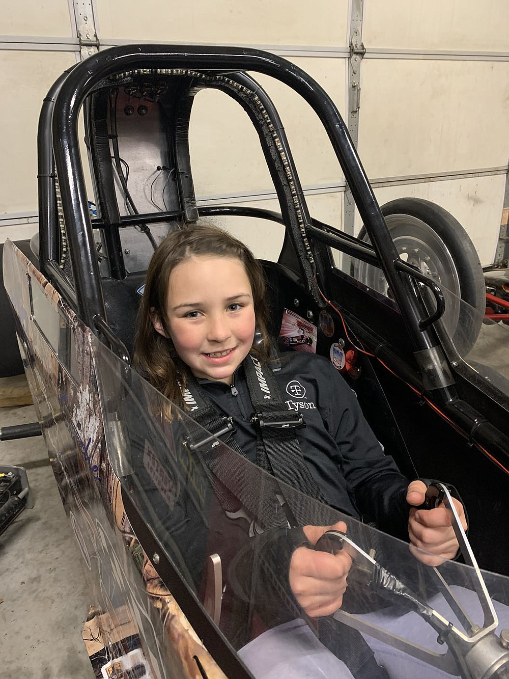 SALLY CARROLL/SPECIAL TO MCDONALD COUNTY PRESS Harper Jensen, 9, loves to drag race. She is guided by her grandfather, Kenneth Trussell, who helps her. Harper's mom, Deni, and cousin, Tristan, also race alongside her.