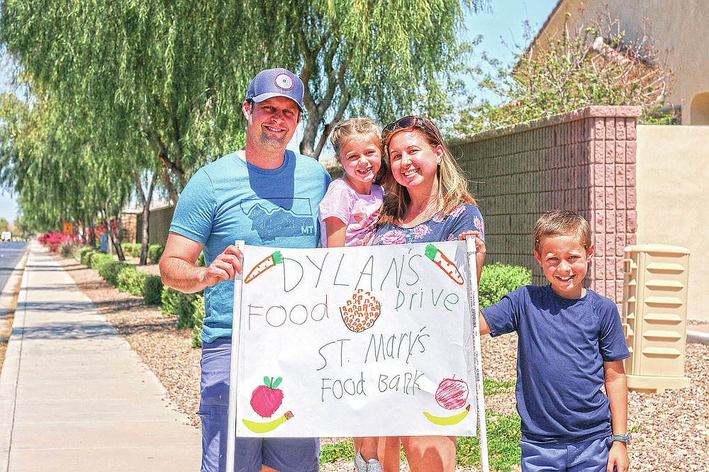 "Nick, Evelyn, Erin and Dylan Pfeifer stand together near their home in Chandler, Ariz., holding a hand-drawn sign promoting a food drive on Saturday, April 3, 2021. Dylan Pfeifer hosted his third food drive since October in response to the coronavirus pandemic. ""It's been hard to interact with people, especially now, so this provides a safe way to do that. I just wanted to provide him a way to make an impact,"" Erin Pfeifer said. (AP Photo/Cheyanne Mumphrey)"
