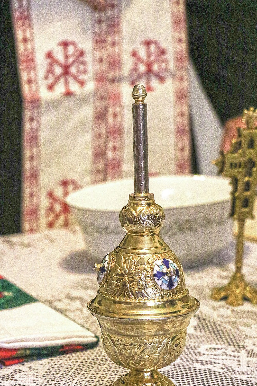 A vessel containing holy water blessed Father Mark Elliott, of St. George Greek Orthodox Church on epiphany sits waiting to be used at a house blessing at Kathleen Chamis' residence Tuesday, March 9, 2021 in Ashland, Ky. After more than a year of fighting an ongoing pandemic, most are ready for a cleansing and Father Mark Elliott of St. George Greek Orthodox Church in Huntington is trying to bring them some peace. (Matt Jones/The Daily Independent via AP)