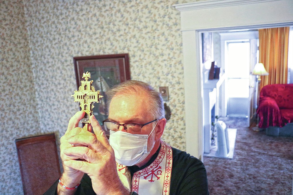 Father Mark Elliott, of St. George Greek Orthodox Church prays at the beginning of the blessing at Kathleen Chamis' residence Tuesday, March 9, 2021 in Ashland, Ky. After more than a year of fighting an ongoing pandemic, most are ready for a cleansing and Father Mark Elliott of St. George Greek Orthodox Church in Huntington is trying to bring them some peace. (Matt Jones/The Daily Independent via AP)